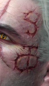 Großansicht der Schriftzeichen in Geralts Gesicht. Das untere entspricht einem 'cha', das obere ähnelt stark dem 'nya' des tibetischen Alphabets.